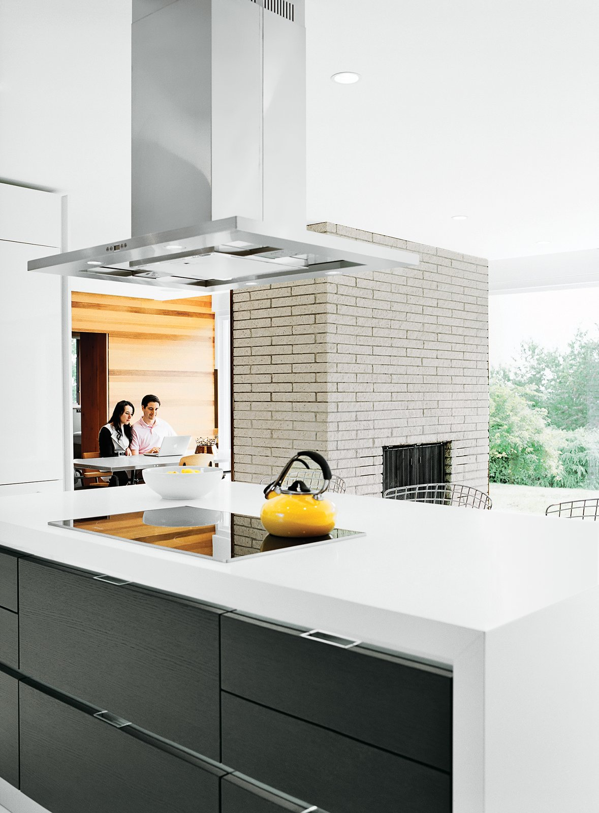The cooktop and oven are Miele, the counter-top is Caesarstone, and the refrigerator is Liebherr. Tagged: Kitchen, Range Hood, and Cooktops.  Photo 6 of 12 in The Midcentury Spirit is Alive and Well in This Hudson Valley Escape