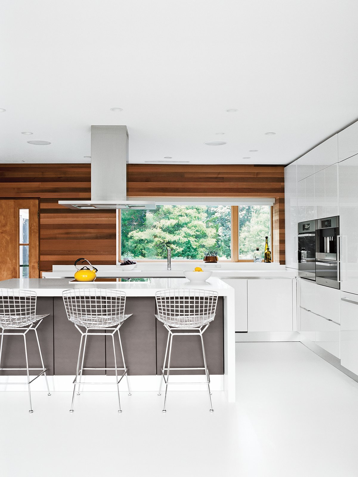 Bertoia bar stools by Knoll are tucked under the island in the Scavolini Scenery kitchen. Jordan replaced the original wood flooring with white resin, a robust surface used in high-traffic environments.  Photo 5 of 12 in The Midcentury Spirit is Alive and Well in This Hudson Valley Escape