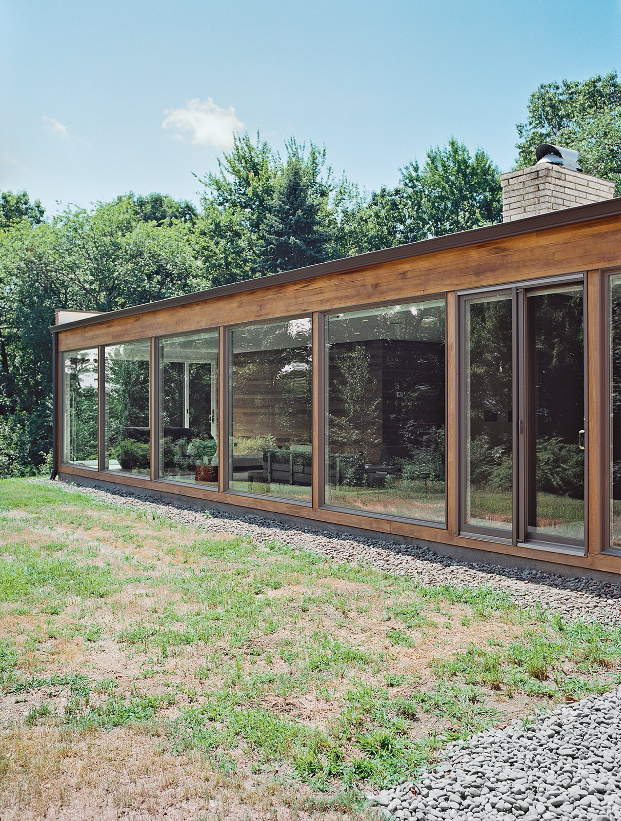 He added floor-to-ceiling windows by Andersen, which allow low winter sunlight to warm the interior in colder months. Tagged: Exterior, Mid-Century Building Type, Flat RoofLine, Wood Siding Material, and House.  Renovations by Annette Luikart from The Midcentury Spirit is Alive and Well in This Hudson Valley Escape