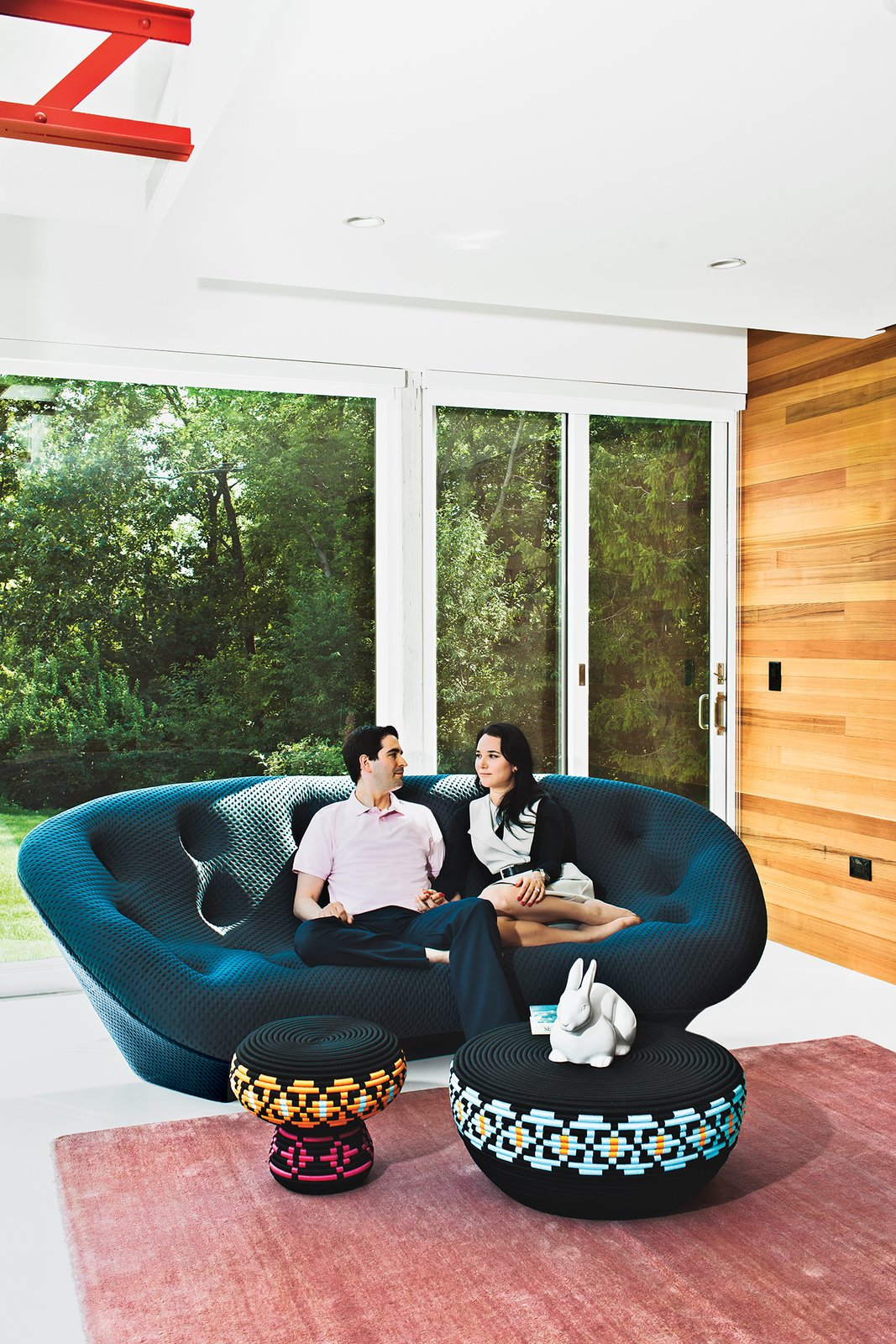 "Steven and Tata relax in their living room. ""The house has always been deemed the 'great escape,'"" says Steven. ""It's a very special place for us."" The Superheroes stool and table are by Swedish designers Glimpt Studio for Cappellini, the blush-colored rug is from ABC Carpet & Home, and the Pan Pan rabbit figurine is by Ligne Roset."