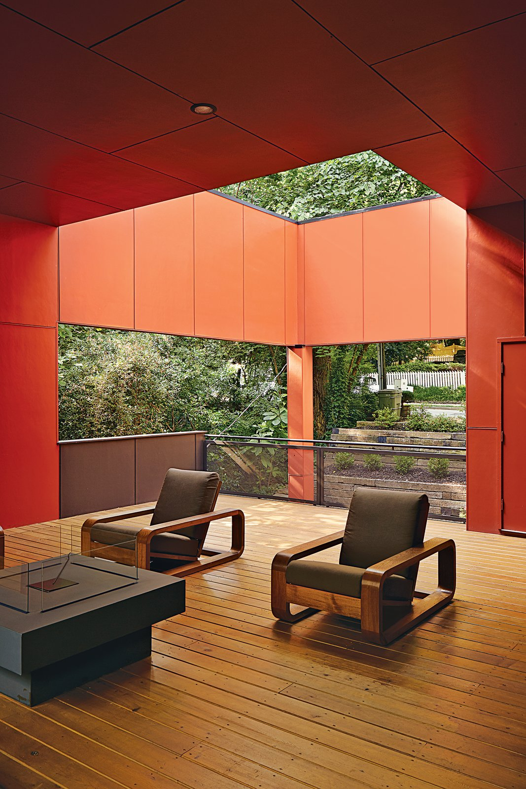 Playing off the work of artist James Turrell, as well as the front porch scheme prevalent in the South, an outside living room is half covered and half open to the leaf canopy overhead, where a pair of teak armchairs are clustered around a Laguna fire table from Restoration Hardware. Tagged: Outdoor, Small Patio, Porch, Deck, and Wood Patio, Porch, Deck.  Photo 1 of 2 in An Affordable Modern Home in Atlanta