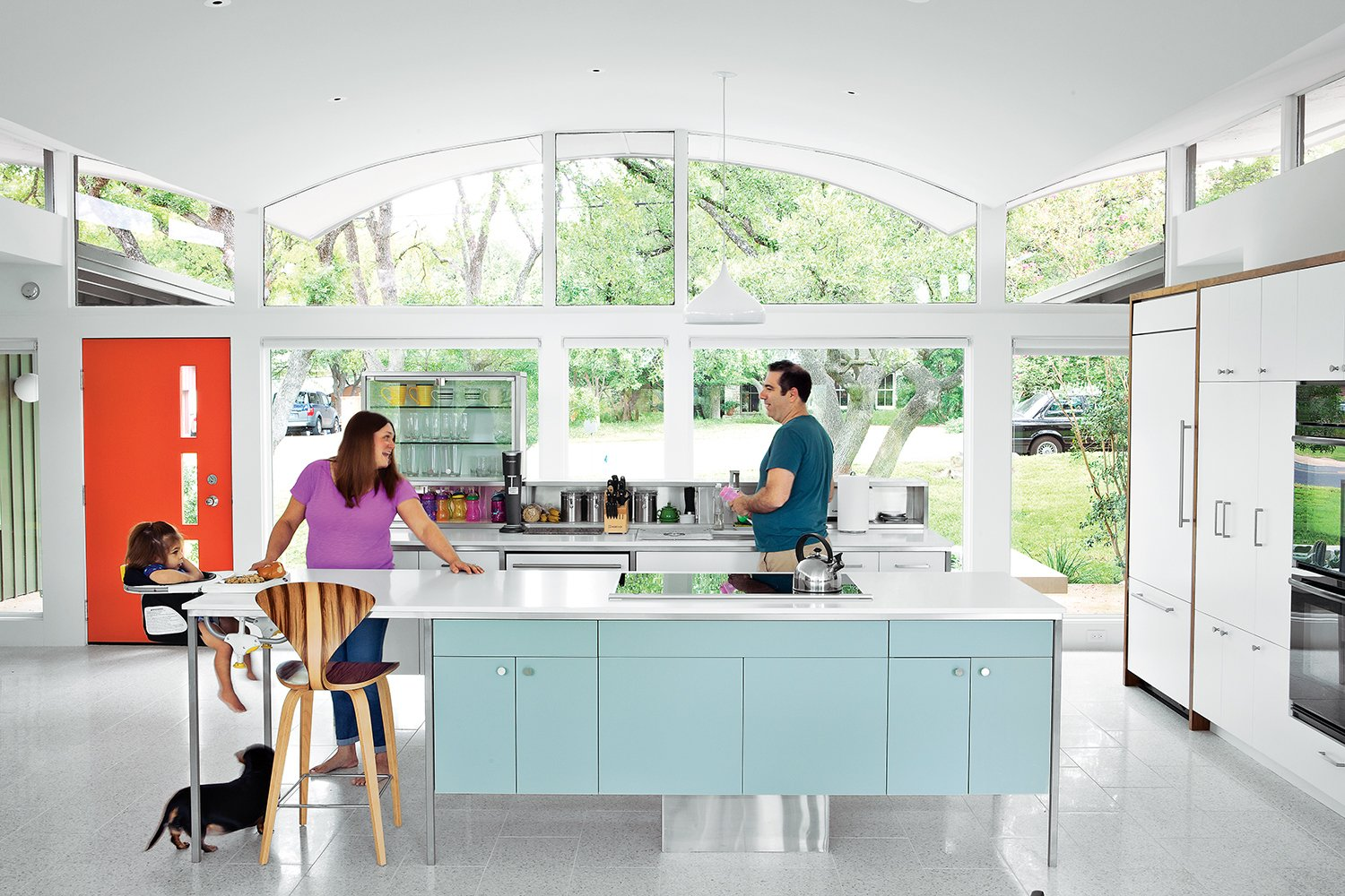 """Though the kitchen fits in with its period surroundings, a few tweaks keep it current. """"It's functional in a way that doesn't feel like the kitchen is in the living room,"""" says architect Rick Black. He explains, """"One of the goals was to make the islands more like furniture than like heavy objects that go all the way to the floor."""" Tagged: Kitchen, Colorful Cabinet, and White Cabinet.  Photo 1 of 11 in A Renovated Midcentury Gem in Austin"""