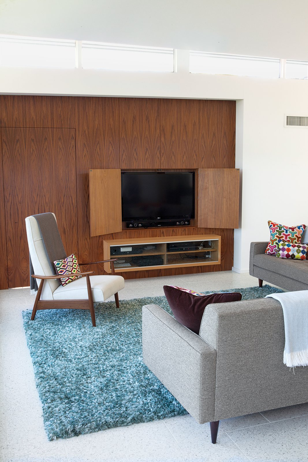 "Architect Cindy Black chose terrazzo tile flooring by Concrete Collaborative over higher-priced competitors because it's a ""little more polished looking"". Before installing the material, the builder had to completely re-level the concrete subfloor, which had settled over time leaving a two-inch gap on one side. The sofa is from Room & Board, and the custom walnut media wall was designed to match the kitchen built-ins. Tagged: Living Room, Concrete Floor, Sofa, and Rug Floor.  Photo 11 of 11 in A Renovated Midcentury Gem in Austin"