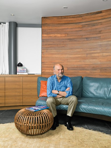 "Kappe sits on a sofa in the media room, which continues the semicircular curve. ""The form came from the [original] client's preference,"" he notes. The rattan ottoman (found in Palm Springs) is by Franco Albini, and the carpet is from Malibu Rugs."