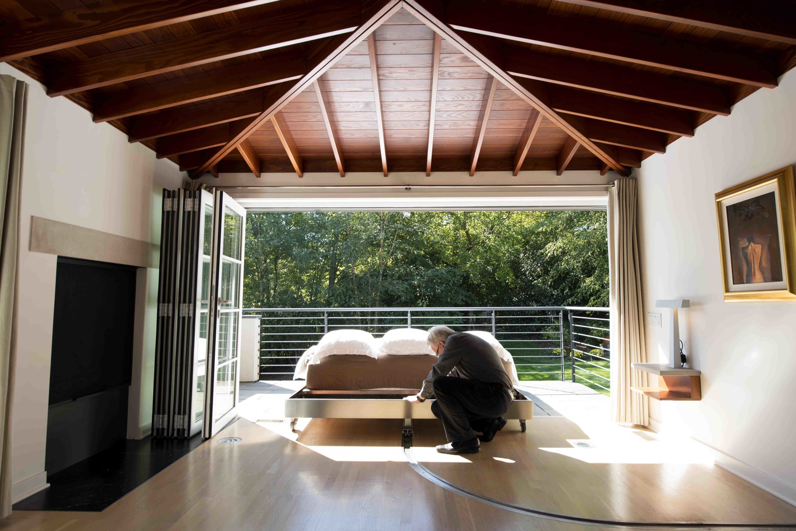 With a gentle nudge, architect John Senhauser pushes a custom bed outside onto the terrace. The bed travels along a metal track set into the white-oak floor. The ceiling rafters are Douglas fir.  Bedrooms by Dwell from The Ultimate Indoor-Outdoor Bedroom