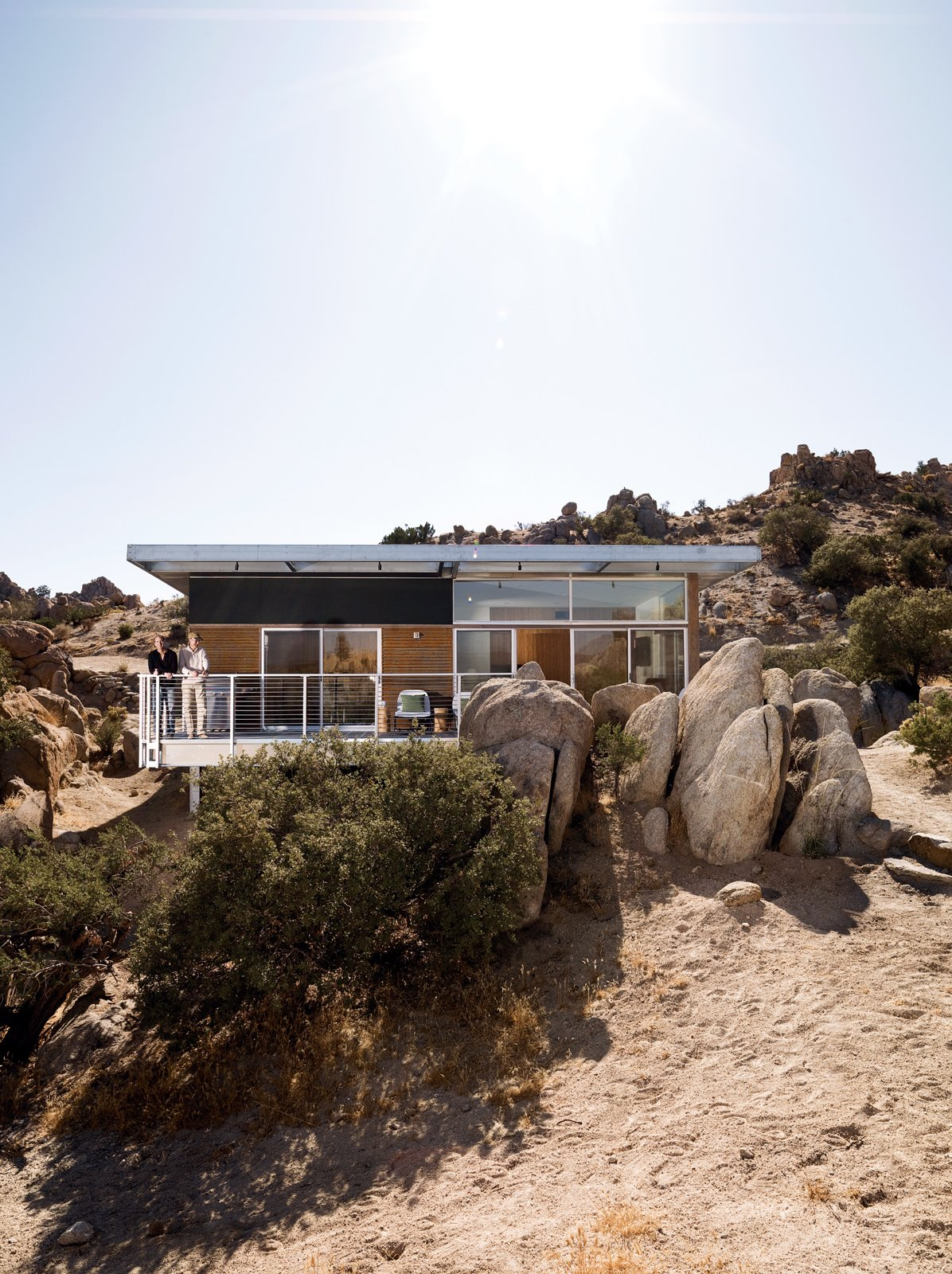 "The Blue Sky prototype house leads a second life as desert getaway for David McAdam and his partner Scott Smith. Tagged: Outdoor, Boulders, Trees, Small Patio, Porch, Deck, Back Yard, Wood Patio, Porch, Deck, Metal Patio, Porch, Deck, and Desert.  Photo 4 of 23 in 20 Desert Homes from Small ""Hybrid Prefab"" Home in the Desert"