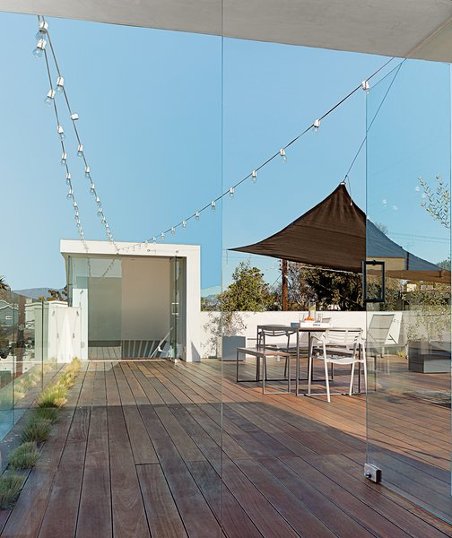 With a fire pit, mobile shades, and drought-tolerant grasses recessed in the Mangaris plank expanse, the roof deck is a communal space in the duplex. The Kookaburra Shade Sail, made of a woven polymer material that prevents mold, can be moved around as needed.