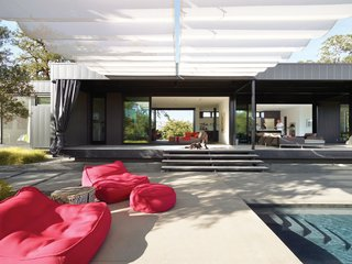 In the foreground are Float beanbag chairs and poufs from Paola Lenti. Mamagreen sofas nestle near the house on the sun-dappled deck. A 9.5-foot-tall shade cloth curtain seals off the entire length of the house when the couple is away, keeping the heat out of the interior and preventing accidental bird suicides against the floor-to-ceiling glass walls.