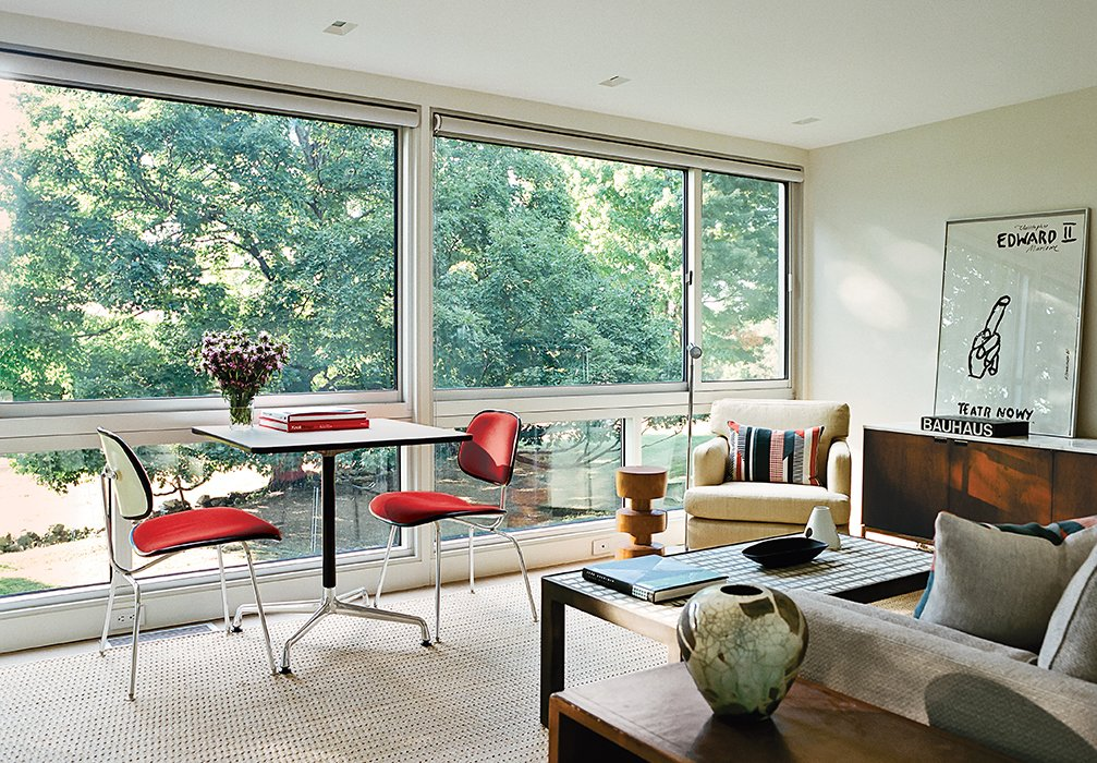 A Universal Base Table and a pair of upholstered Molded Plywood Dining Chairs, all by Charles and Ray Eames for Herman Miller, are positioned by the window. Tagged: Living Room, Chair, Sofa, and Rug Floor.  Photo 2 of 5 in These 5 Transformations Show Why Challenging Renovations Are Worth It