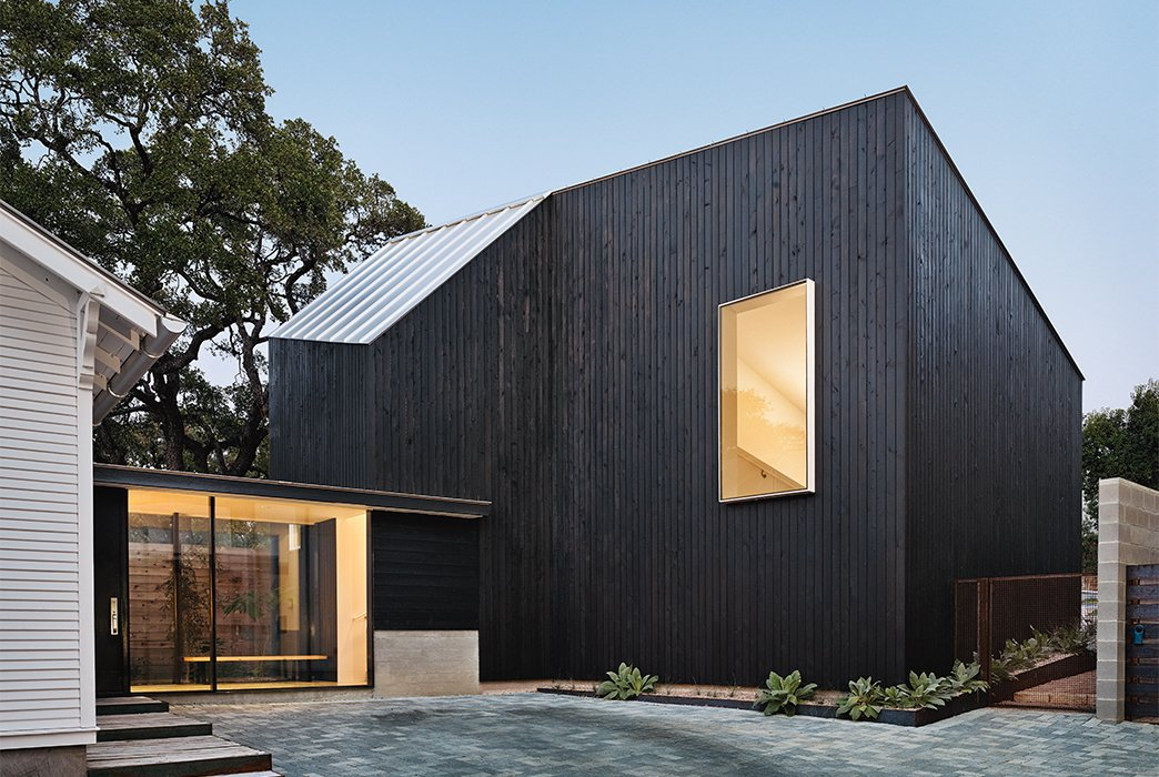 The addition, which has cypress paneling and a metal roof, is united with the renovated 1920s bungalow via a glass pavilion. Tagged: Exterior, Wood Siding Material, and House.  Photo 5 of 12 in 1920s Bungalow Plus Modern Addition Equals Perfect Austin Home