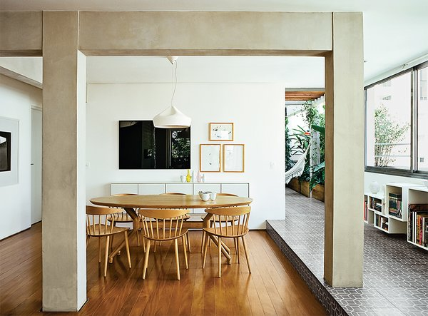 They replaced the tile floor with perobinha, an inexpensive local wood, and enclosed part of the terrace, integrating it into the dining room. J104 chairs by Jørgen Bækmark for Hay are arranged around a freijo wood dining table by Etel Carmona.