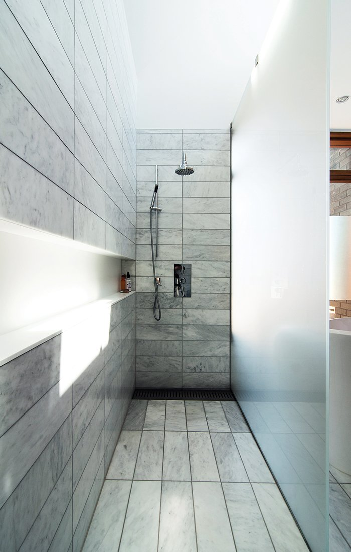 """The standing shower is set off by etched-glass panels supported by stainless-steel hardware. There is no threshold; instead, the tile within the shower zone slopes down very slightly to a floor trough with a custom stainless-steel grille. Along the wall, a Corian shelf—""""the longest soap dish in the world,"""" resident Don Evans jokes—runs the length of the space. Tagged: Bath Room, Enclosed Shower, and Full Shower.  Photo 9 of 10 in 10 Best Modern Showers to Inspire Your Bathroom Renovation from A Toronto Tudor Becomes Bright, Luxurious Home"""