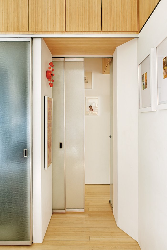 The architects designed the bamboo-plywood storage compartments above the hallway, bathroom, and bedroom closet. Tagged: Hallway and Light Hardwood Floor.  Photo 7 of 12 in Bright Renovation of a Tiny Manhattan Apartment