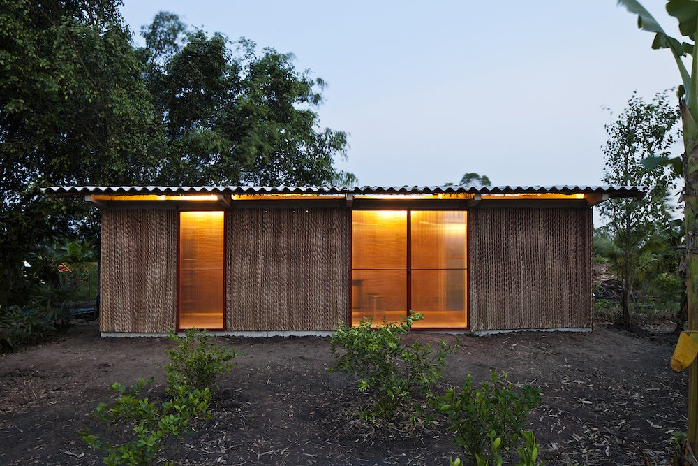 Vo Trong Nghia Architects utilized passive design strategies and a double roof, constructed from Nipa palm and corrugated cement, to ventilate the home, an important consideration in a humid, tropical environment.  Photo 2 of 7 in A $4000 Prefab Prototype in Vietnam