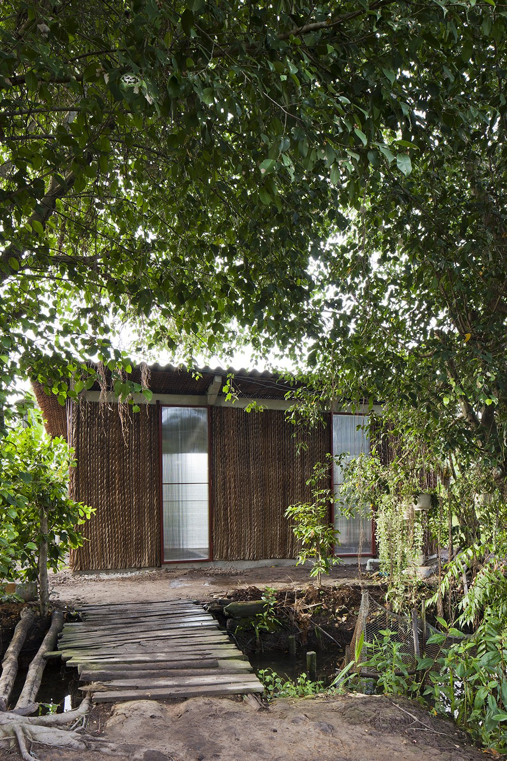 The key to the home's relative affordability is the selection of materials. A prefabricated frame is covered in natural materials, such as Nipa palm, that can be easily replaced and maintained, while seamlessly blending in with the surrounding environment.  Photo 3 of 7 in A $4000 Prefab Prototype in Vietnam