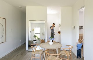 How One Family of Three Does It All in 675 Square Feet - Photo 2 of 14 - A large metal floating mirror from Restoration Hardware seemingly doubles the 675 square feet of the Schmidt-Friedlander apartment in Windsor Terrace, Brooklyn. The family of three dines at an oak table from Canvas Home, with Wishbone chairs by Hans Wegner. Decorators White paint by Benjamin Moore and oiled Hakwood European oak flooring are used throughout.