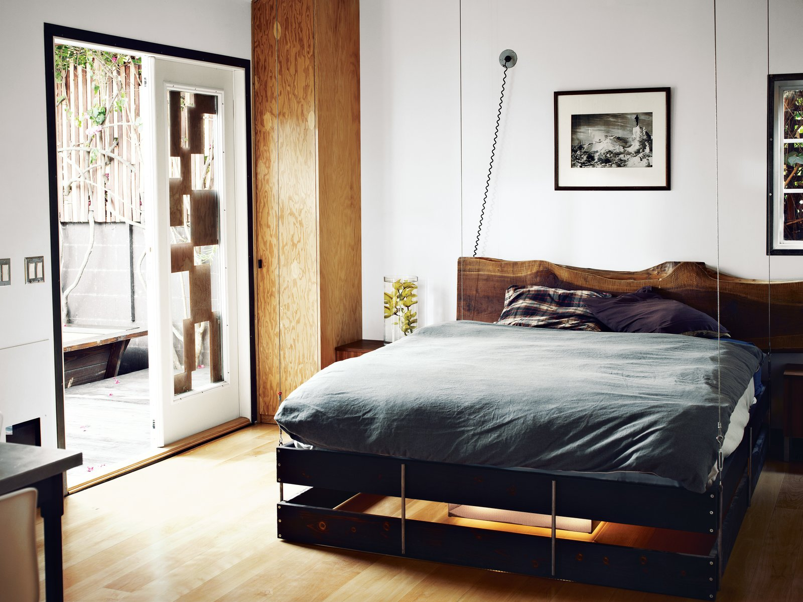 The bed was designed to hang from the ceiling and can be hoisted up and pulled down as needed. Tagged: Bedroom, Bed, and Medium Hardwood Floor.  Bedrooms by Dwell from The Tiny Hollywood Home of Mad Men's Vincent Kartheiser