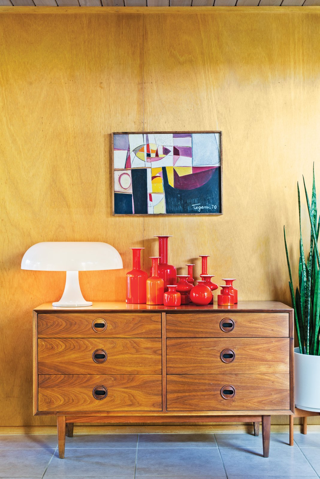 A vintage chest of drawers supports the playful forms of a Nesso lamp, designed by Giancarlo Mattioli for Artemide, and a collection of Holmegaard ceramics.  Photo 1 of 15 in Modern Furniture Fit for a Classic Eichler