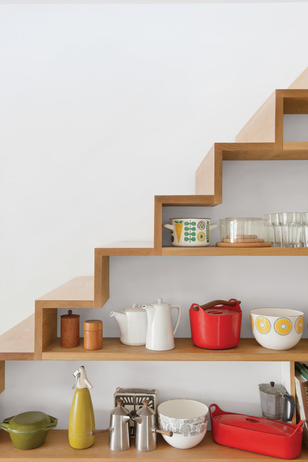 A closer look at the shelving built into the staircase in the kitchen. Tagged: Storage Room and Shelves Storage Type.  Close ups • kitchen by Tanya Pavlova from An Obsessed Designer Fills Her Home with Vintage Finds