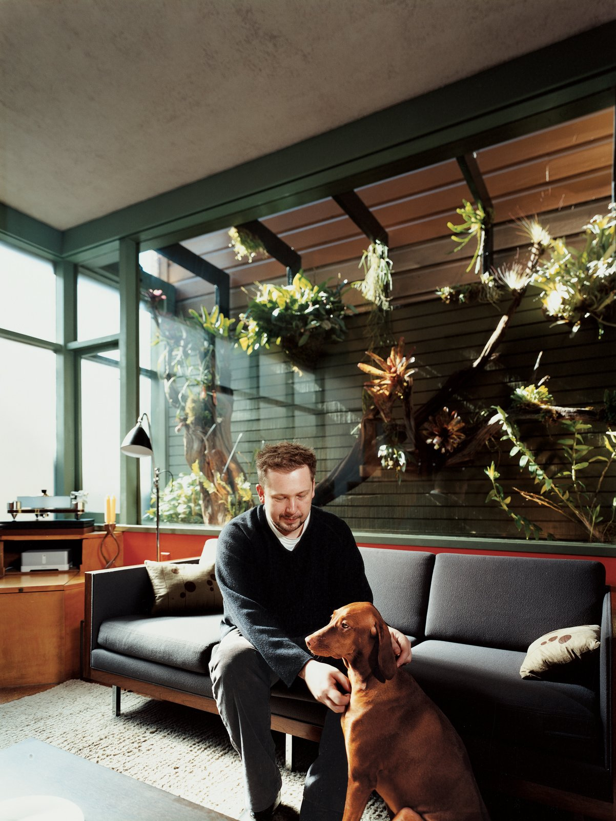 Farnham and Kasia sit in front of the home's most impressive feature: an enclosed atrium overlooking the living area. In 2007, Dale Loughins outfitted the atrium with all manner of exotic epiphytes and an automated misting system. Tagged: Living Room and Sofa. Mid-Century Mash-Up - Photo 3 of 14