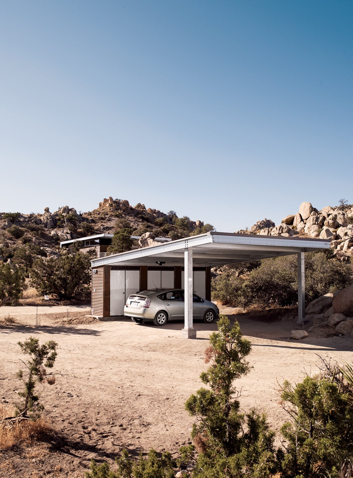 "The carport stands apart from the home and is topped with Solar World's Sun Module photovoltaic panels. McAdam and Smith have grown quite used to their small electric bills.  Photo 8 of 10 in Small ""Hybrid Prefab"" Home in the Desert"
