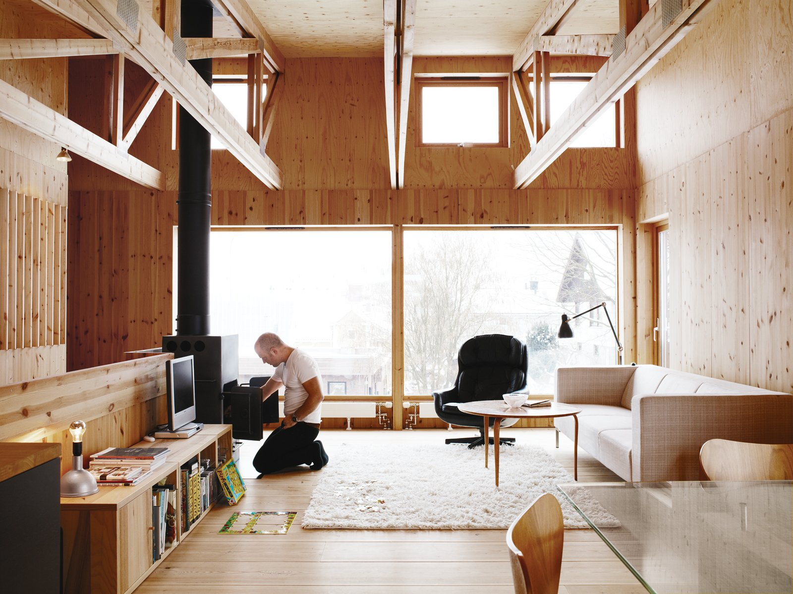 Bornstein's living room features an intriguing collection of furniture. The sofa is made by Swedish manufacturer Ire. The 1970s wood burner was a secondhand store find, and the wood table, by Bruno Mattson, was found in a bin at a recycling station. He inherited the lounge chair from his parents.  Tips for Creating a Comfortable Living Room by Drew McGukin from Knotty by Nature