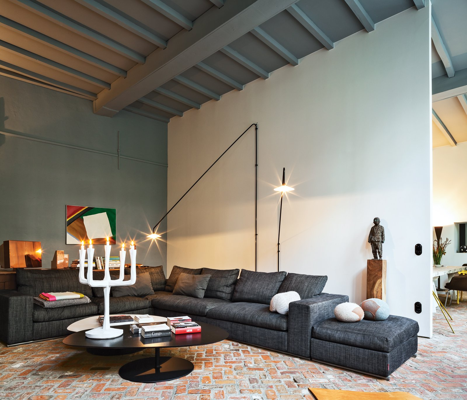 The room also contains a sofa by Flexform, cushions from textile firm Chevalier Masson, a Jens Fager candelabra, and a painting by Roger Raveel. Tagged: Living Room, Brick Floor, Sofa, Sectional, Floor Lighting, and Table Lighting.  Living Rooms by Lara Deam from An Eclectic Living Room in Antwerp