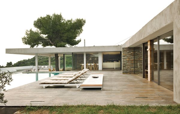 Stone walls, a pine tree exploding out of a deep overhang, iroko decking, outdoor rooms, a glassy swimming pool, and endless views of the sea make this home a paragon of indoor-outdoor living.