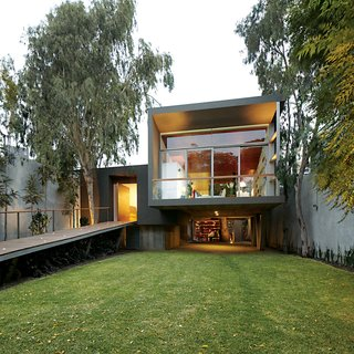 A Modern Concrete Home in Peru - Photo 1 of 13 - The entrance is reached via a long ramp perforated by uplights.