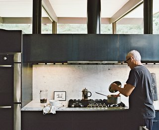 10 Stunning Ways to Use Black in Your Kitchen - Photo 7 of 10 - The couple made the most dramatic changes in the kitchen. They installed Carrara marble and custom oiled-steel cabinetry. The artwork is by Cecil Touchon. Near the Wind Crest cooktop is a Bosch oven.