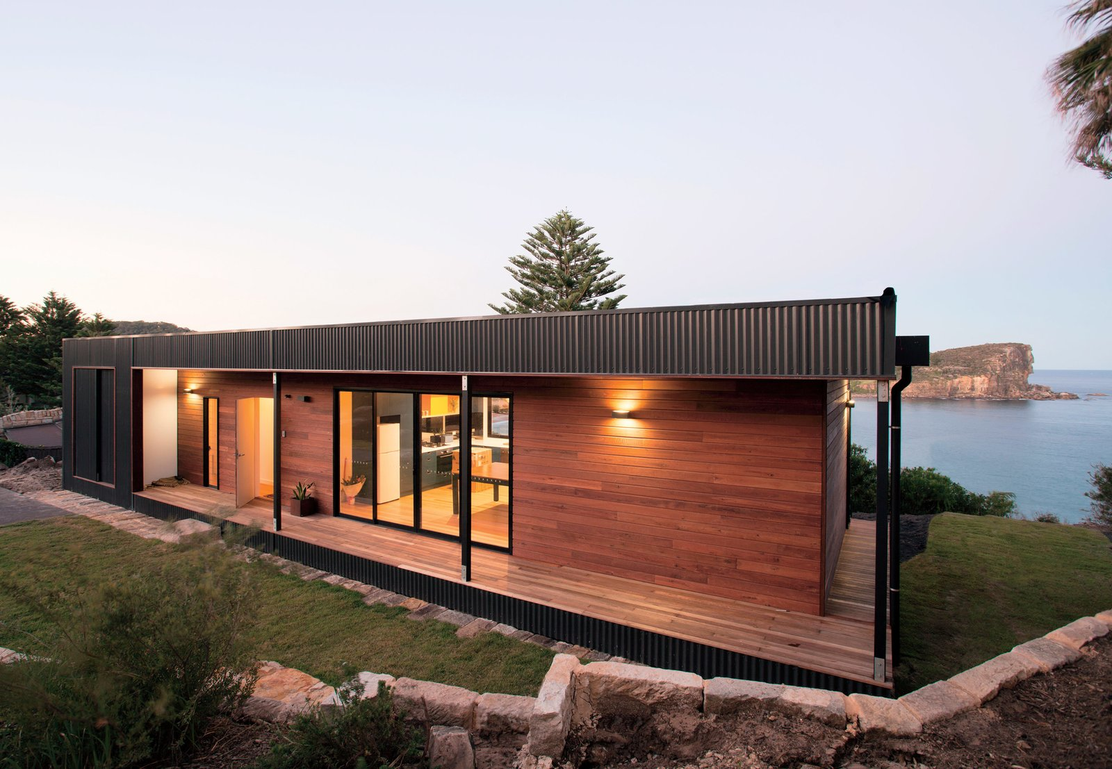 A prefab house designed by ArchiBlox on the northern beaches of Sydney sustains high winds and spray from the surf, so the firm wrapped the exterior in marine-grade Colorbond Ultra steel. Panels of Queensland blue gum, a native Australian hardwood, clad the street-side facade, which is protected from the harsh climate. Tagged: Outdoor, Back Yard, Grass, Shrubs, Wood Patio, Porch, Deck, and Small Patio, Porch, Deck.  Modern Beach Homes in Australia by Matthew Keeshin from A Dramatic Cliffside Prefab Steps from the Beach in Australia