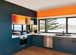 Inspired by the sea and sand, the couple chose blue and orange joinery colors. The oven, cooktop, range hood, and dishwasher are by Bosch.