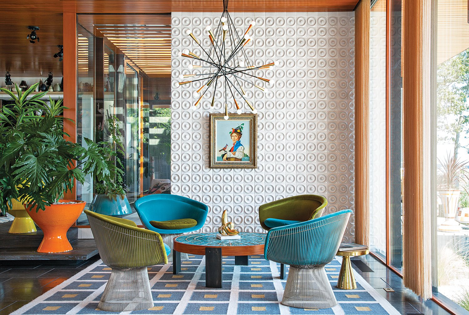 """There's no right answer except to play and experiment,"" Adler says about furnishing the interior. He reupholstered vintage Warren Platner chairs with velvet from Kravet. Drawings by Eva Hesse inspired the custom ceramic wall tile. Adler also created the coffee table, rug, planters, and gold stool. The pendant lamp is from Rewire in Los Angeles and the artwork is by Jean-Pierre Clément. Tagged: Living Room, Ceiling Lighting, Coffee Tables, Chair, Rug Floor, and Pendant Lighting.  Photo 3 of 10 in Jonathan Adler and Simon Doonan's Shelter Island Vacation Home"