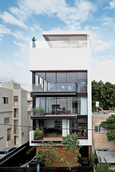 Tall and surprisingly open, the Tel Aviv Town House by Pitsou Kedem Architects continues in the tradition of its Bauhaus-inspired neighbors with a white facade and black window frames.