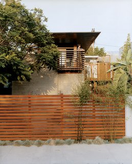 Sustainability in Stages - Photo 2 of 6 - Trellis-like balcony railing cue the exposed timber frame extending over the house. The balcony and fence are made from sustainably harvested ipe wood.