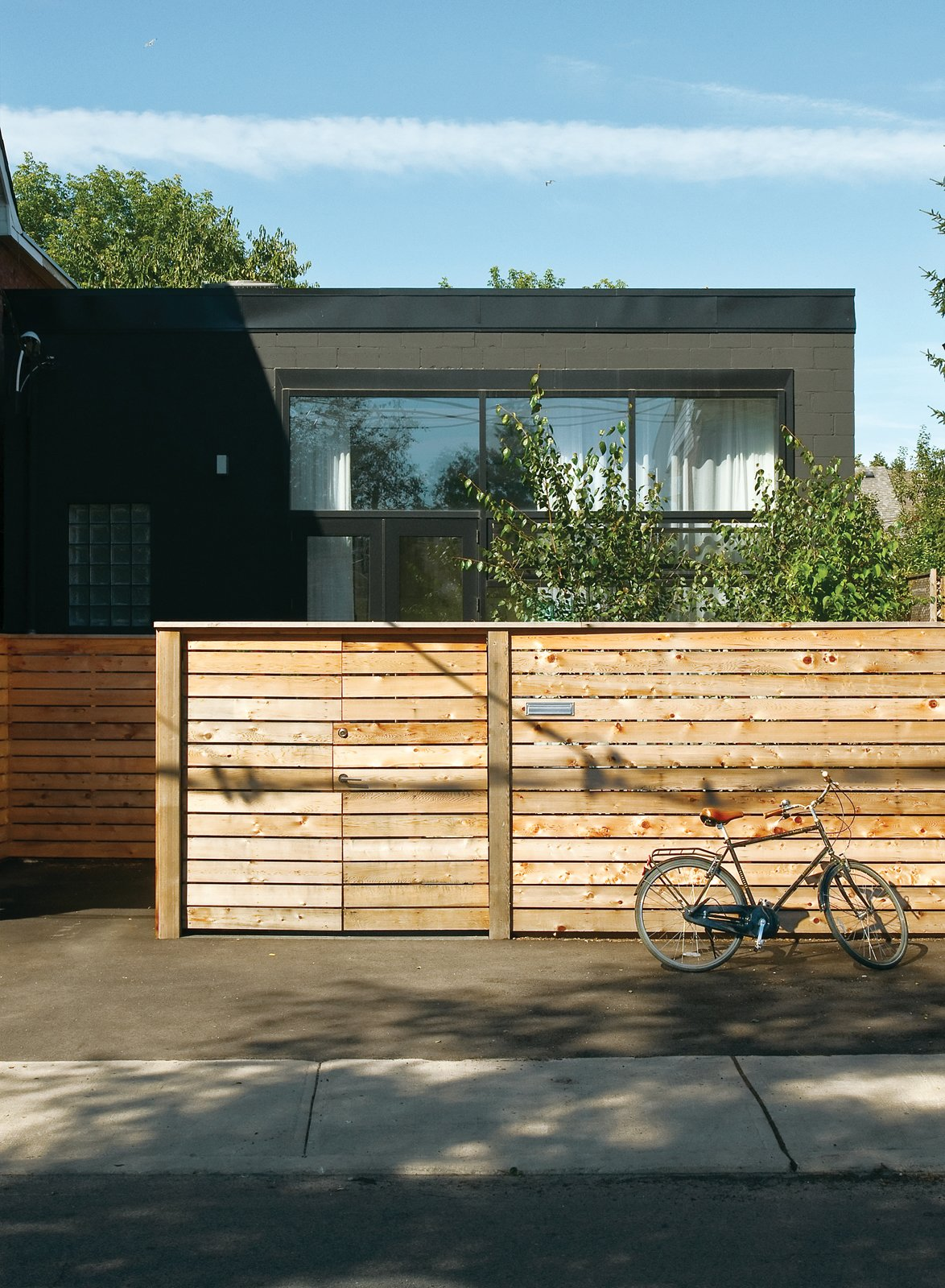 Monkman's house has a quiet presence, its front half hidden behind a fence of cedar two-by-sixes.  30+ Best Modern Fences by William Lamb from An Art Studio That Would Make Picasso Jealous