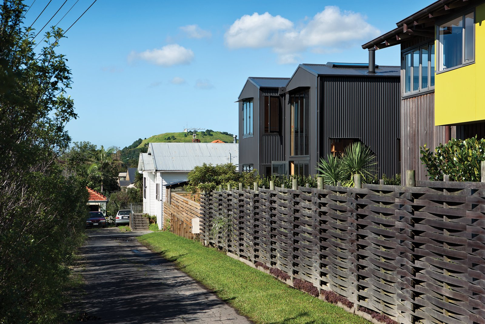 With its pitched roof and verticality, the house blends with the surrounding seaside neighborhood yet remains architecturally distinct thanks to its aluminum cladding. Tagged: Outdoor, Wood Fences, Wall, and Horizontal Fences, Wall.  Photo 5 of 8 in Rock the Boat