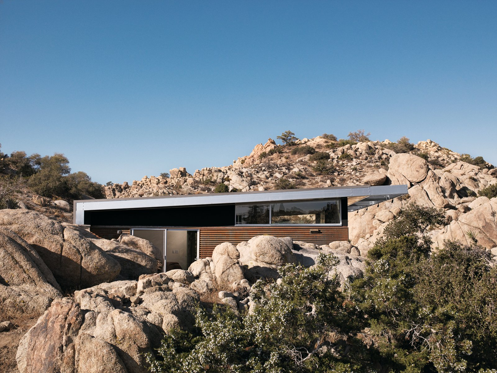 "For all its hard environmental work, one of the most immediate of the Blue Sky Home's pleasures is how it sits so snugly in its desert surroundings. Tagged: Outdoor, Desert, Boulders, Trees, and Shrubs.  Off the grid by Michela O'Connor Abrams from Small ""Hybrid Prefab"" Home in the Desert"