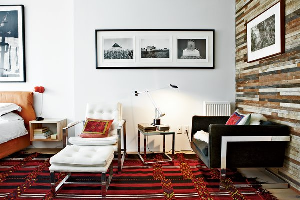 In the master bedroom, the couple opted for Artemide lighting: Vintage Eclisse table lamps by Vico Magistretti hang over the nightstands and a Tizio table lamp by Richard Sapper rests on a side table. The lounge chairs are vintage finds, and the rug is a Bedouin design purchased in Jerusalem.