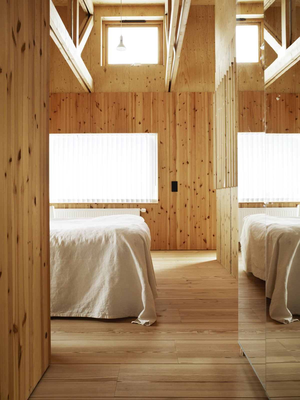 The white linens appear almost ghostly against the natural grain of the wood and muted glow of the window's winter light. Tagged: Bedroom, Light Hardwood Floor, Bed, and Pendant Lighting.  Photo 9 of 11 in 10 Warm Wood Floors from Knotty by Nature