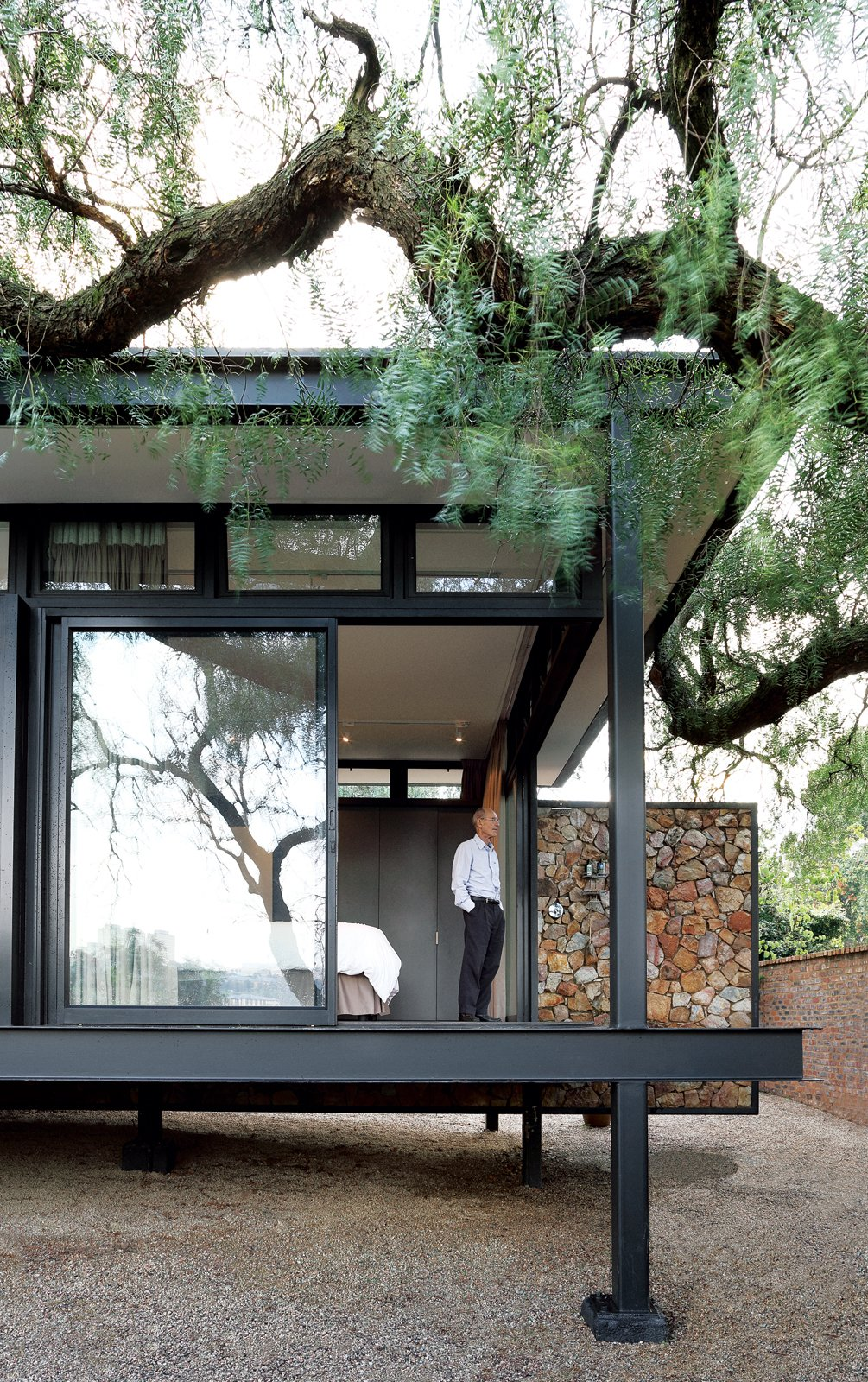 Architect Georg van Gass adds a delicately poised cantilevered exterior wall that appears to slice the deck in half. Photo by: Elsa Young Tagged: Exterior, House, Metal Roof Material, and Metal Siding Material.  Design Itinerary: South Africa by Kelsey Keith from A Mies van der Rohe-Inspired Cottage in Johannesburg