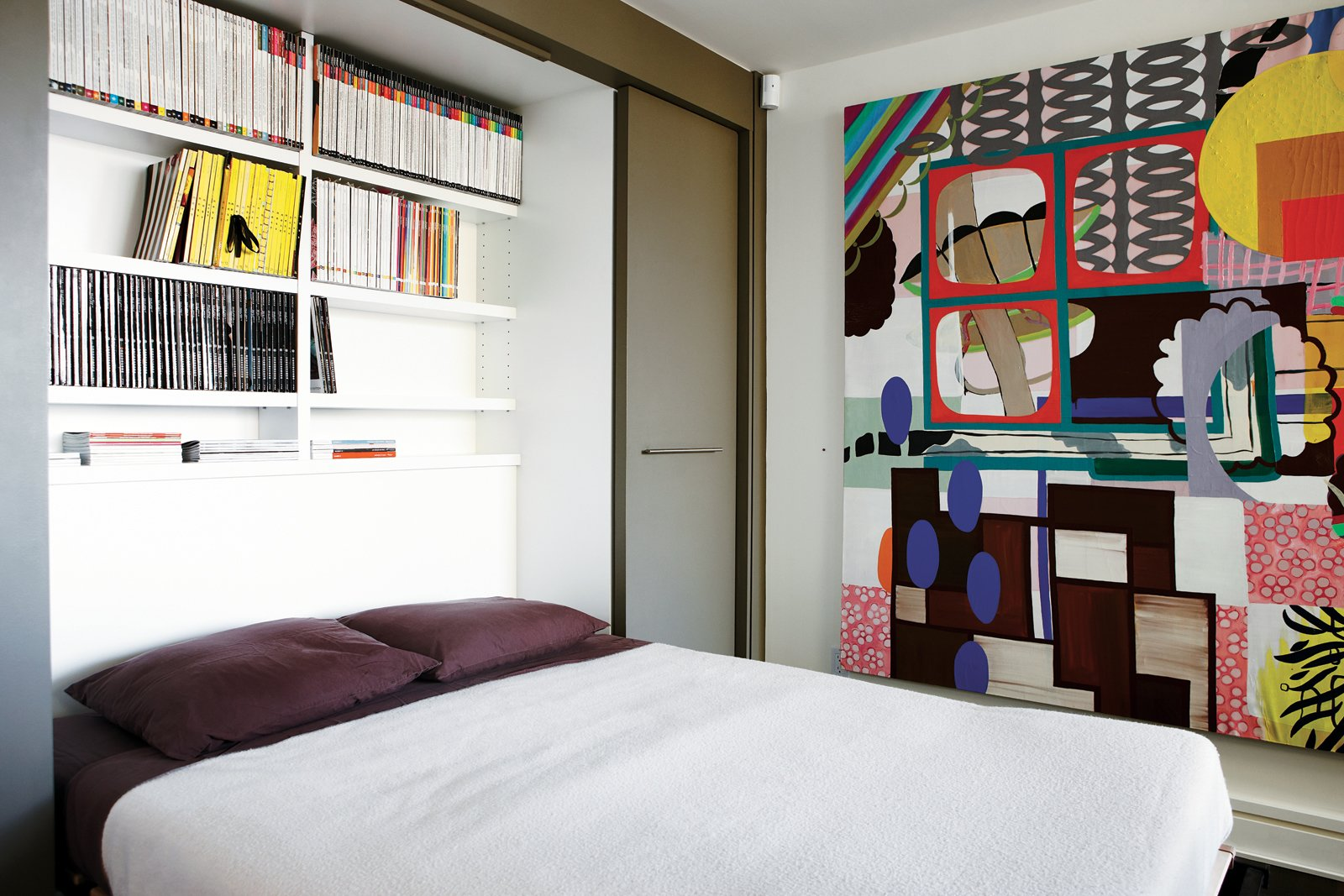 Montague's office doubles as a guest room thanks to a Murphy bed that folds out to reveal shelves stocked with design magazines. The painting is Untitled (Corner Rainbow) by Elizabeth McIntosh. Tagged: Bedroom, Bed, and Shelves.  Bedrooms by Dwell from Party-Friendly Apartment in Toronto