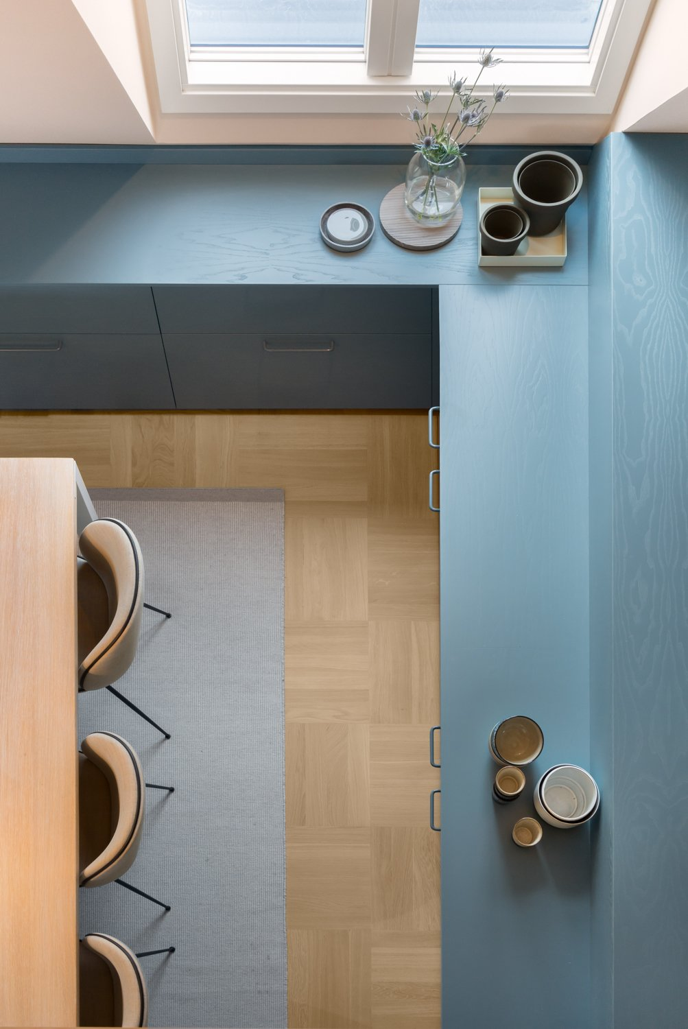 "A custom blue-gray built-in storage unit, which includes shelving, cupboards, and drawers, runs throughout the home, connecting the rooms. ""The tone is calm and creates a dark base,"" Wåhlin says. ""The apricot pink, together with the sandy colors, reflect light but give a warmth to the space and contrast with the blue tones. Together, they become dynamic.""  Loft by David Christopher Kinikin from There's Not a Single White Surface in This Comfy Stockholm Loft"