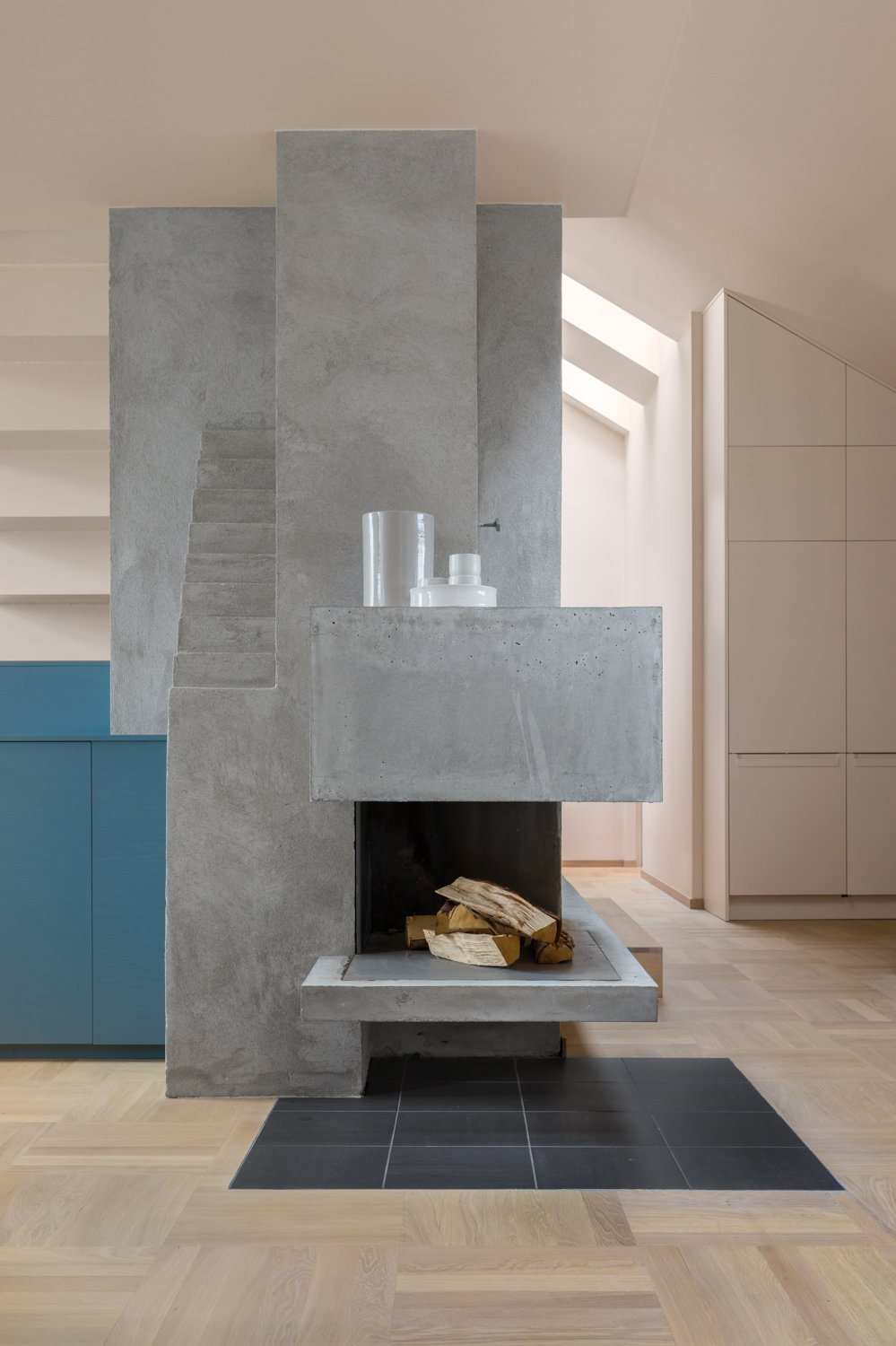 The sculptural fireplace, covered in plaster, contrasts with oak parquet floors.