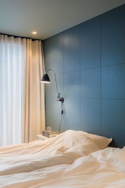 NOTE designed the wood blue-gray wall covering in this bedroom. A chrome Bestlite BL6 wall lamp by Gubi hangs near custom-made curtains, created using fabric by Astrid.
