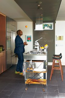 Party-Friendly Apartment in Toronto - Photo 2 of 15 - Architect David Anand Peterson designed the custom millwork and shelving in Montague's kitchen. The stainless steel island is by Bulthaup. The stools are vintage and were designed by Erik Buck. Montague was thrilled to spot the same ones adorning Don Draper's apartment in the latest season of Mad Men.