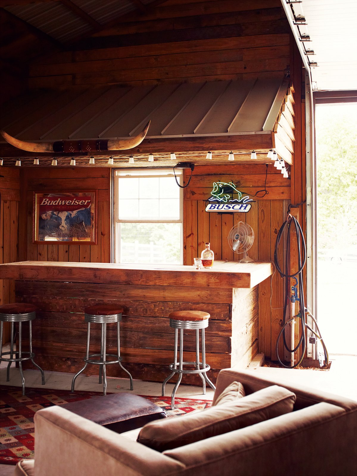 Inside, Paul often dispenses whiskey to friends from behind the rustic bar. Tagged: Dining Room, Bar, Chair, Stools, Rug Floor, and Ceiling Lighting.  Photo 6 of 10 in A Modern Farmhouse Recalls Old-Time Americana