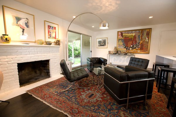 """The elder Popp bought the Le Corbusier chairs in the '80s and the Arco Flos lamp in the '70s; the Philippe Starck barstools were purchased recently for the apartment. The antique rugs are from Ronald Popp's collection, and the art is by mostly Bay Area artists. To help control costs, Popp worked with much of the existing 1950s building's elements, such as the brick fireplace, giving it a coat of white paint """"to provide a better background for the art."""" Just off the living room, accessed through a floor-to-ceiling glass door, is a garden for Popp's father."""