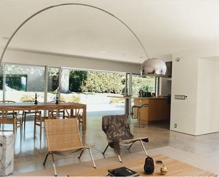A 14-foot-wide opening at the rear of the house contributes, along with the concrete flooring, to an almost seamless transition from indoors to the patio. A spate of mid-century furnishings includes chairs by Hans Wegner and Poul Kjærholm and an Achille Castiglioni Arco lamp.