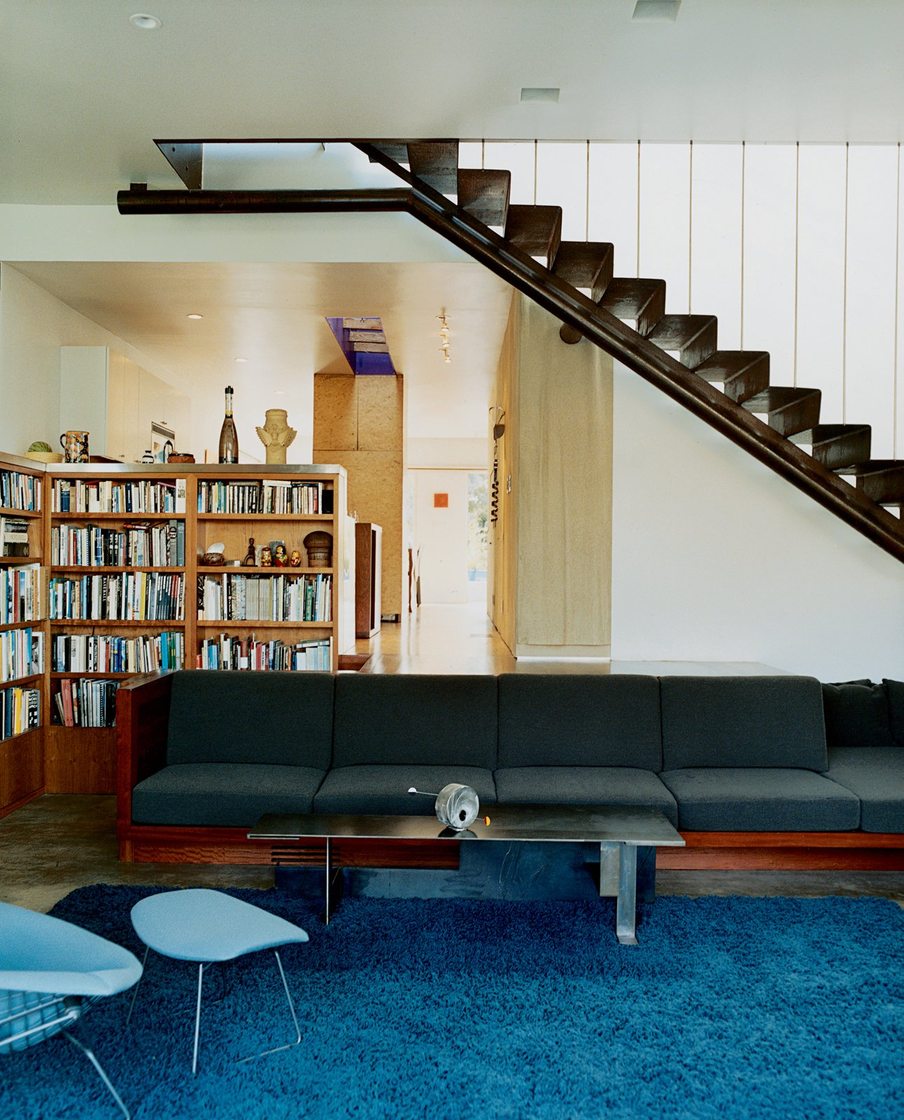 A built-in sofa with Design Tex upholstery marks the boundary between the two-level addition and the bungalow. Leading up to the master bedroom, a perforated metal staircase, lit from above, casts a Sigmar Polke–like shadow grid on the concrete floor.  190+ Best Modern Staircase Ideas by Dwell from Solar Inspiration